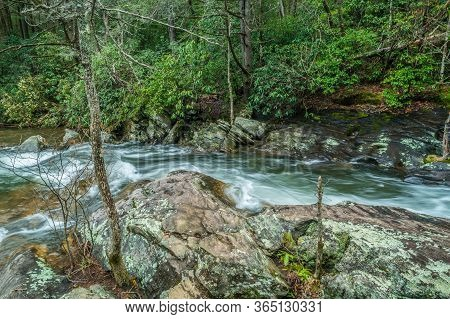 A Fast Moving Rushing River Flowing Downstream From The Mountains Through The Rock And Boulders In T