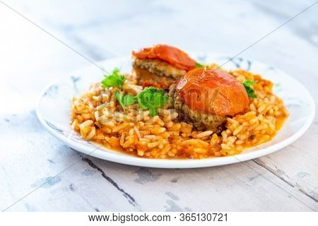 stuffed tomatoes with rice on a white plate