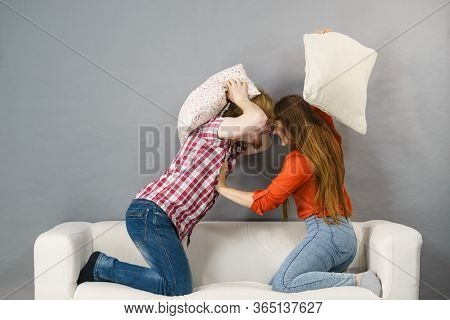 Angry Couple Having Pillow Fight. Brother And Sister Having Conflist On Sofa.