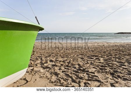 Bow Of A Green Boat Aground On Cubelles Beach In The Mediterranean Sea In A Sunny Day Of Summer. Bar