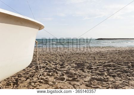 Bow Of A White Boat Aground On Cubelles Beach In The Mediterranean Sea In A Sunny Day Of Summer. Bar