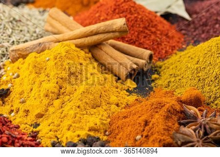 Various fragrant spice market. Heap different Indian Spices on wooden table. Assortment spices and herbs for cooking