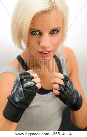 Rough woman ready to fight with boxing bandage gloves