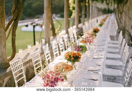 Wedding Dinner Table Reception. A Very Long Wedding Table Going Into Perspective. Bouquets Of Yellow