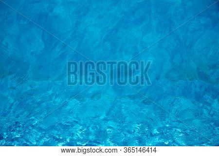 Blue and crystalline water of a swimming pool with a sunny day