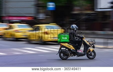 Bucharest, Romania - May 07, 2020: An Uber Eats Food Delivery Courier On A Scooter In High Speed. Re