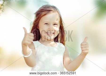 The Little Girl Happy Toddler Kid Showing Thumbs Up Gesture With Hands,  Outdoors Green Tree Park On