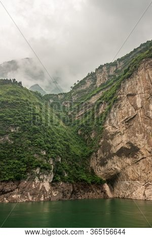 Xiangxicun, China - May 6, 2010: Xiling Gorge On Yangtze River. Cleavage Separates Brown Rock Cliff