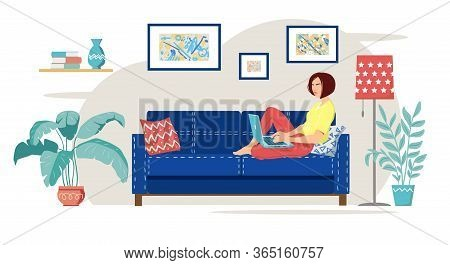 A Young Woman Is Sitting On A Blue Sofa And Working From Home With A Laptop. Cozy Modern Living Room