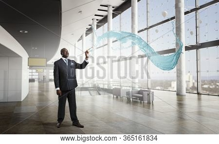 Conceptual image of ambitious and creative businessman in black suit holding paintbrush in hand