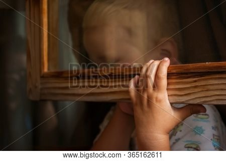 A Small Child Is Afraid Of Punishment And Hides Behind A Window Frame. Frightened Toddler Boy Lookin