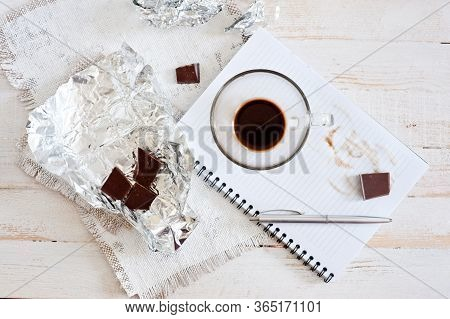A Cup Of Coffee, Chocolate, A Sheet Of Paper And A Pen On A White Wooden Surface. Background For Wor