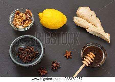 Health Remedy Foods For Cold And Flu Relief With Lemon, Ginger, Honey And Walnuts On A Black Backgro