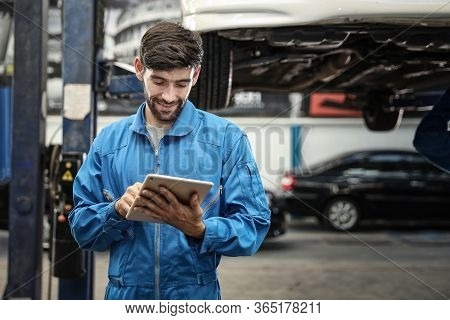 Mechanic Using Screwdriver For Repair With Repair Equipment Standing Under The Car In Maintainance S