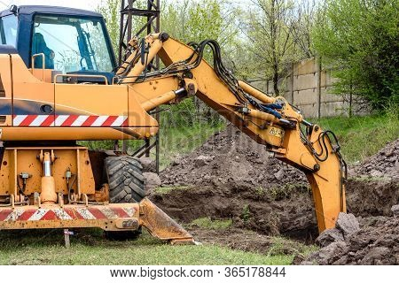 Yellow Excavator On A Construction Site Against Blue Sky. The Modern Excavator Performs Excavation W