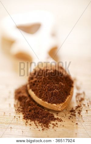 ground coffee powder in heart shape wooden spoon, shallow dof