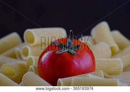 Tomato Laid On Italian Rigatoni Pasta With Dark Background