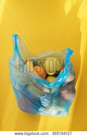 Oranges, Bananas, Apples, Avocados Lie In A Cellophane Plastic Blue Bag On Bright Yellow Background