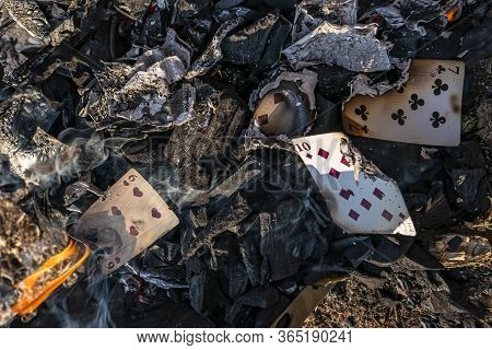 Burnt Playing Cards In Smoke Ashes After Fire Flame. Struggle With Gambling Addiction