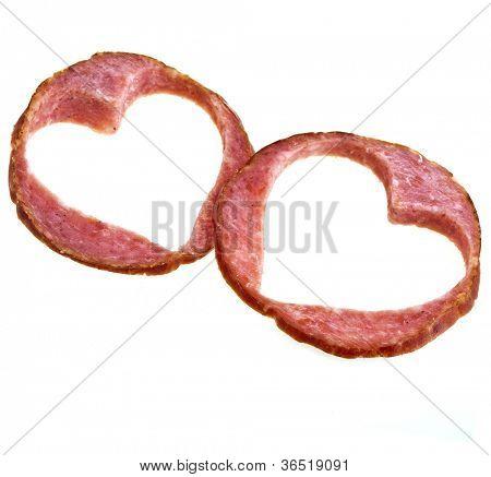 slices of salami with a hole in the form of heart isolated on a white background