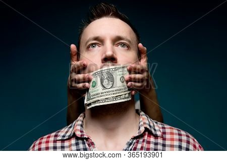 Hands From The Darkness Cover The Mouth Of A Working Man With Small Dollars. Cheap Silence And Corru