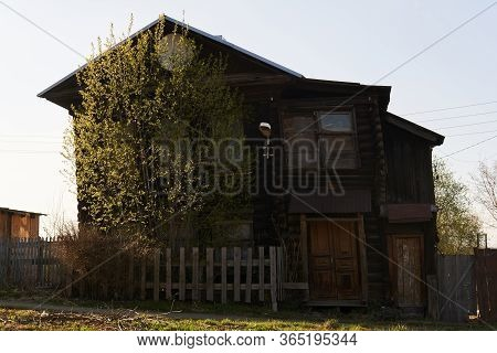 Silhouette Of An Old Decrepit Rickety Two-story Log Cabin In The Spring Sunshine