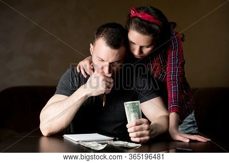 Husband And Wife Calculate Family Budget. The Husband Seriously Considers And Holds Money, The Wife