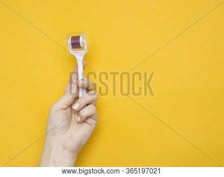 Mezoroller, Dermaroller, Mesotherapy Skin Tool In A Woman's Hand On A Yellow Background. Copy Space.