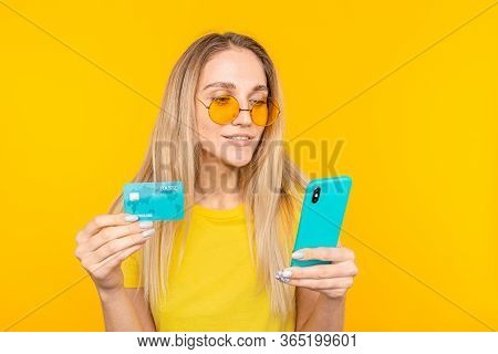 Portrait Of A Young Blonde Girl Showing Plastic Credit Card While Using Mobile Phone Isolated Over Y