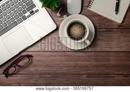 Old Wood Desk Table With Black Coffee  And Laptop Computer, Notebook And Eye Glasses. Top View With