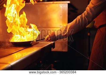 Flambe. Fire In Frying Pan. Professional Chef In A Commercial Kitchen Cooking. Man Frying Food In Fl