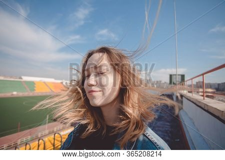 A Girl Stands On The Top Rows Of A Football Stadium