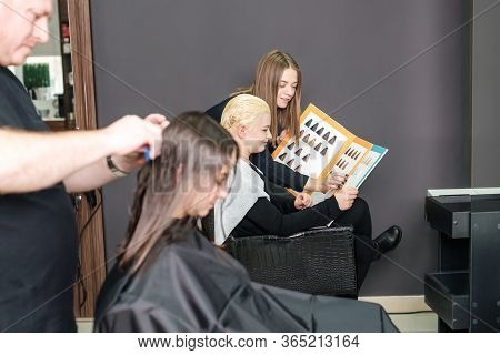 Young Woman With Hairdresser Are Choosing Hair Color From Palette Samples At Beauty Salon. Choice Ha