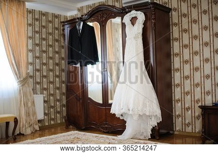 Beautiful And Elegant White Wedding Dress And Man Groom Wedding Suite Hanging On A Wardrobe In Antic