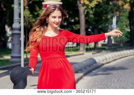 Smiling Young Woman In Red Dress Is Catching Taxi On The City Street. Pretty Adult Girl Is Catching