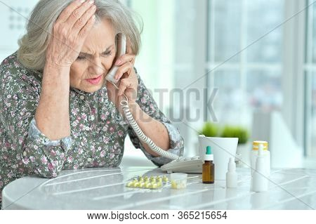 Portrait Of Beautiful Ill Senior Woman Calling Doctor And Posing At Home