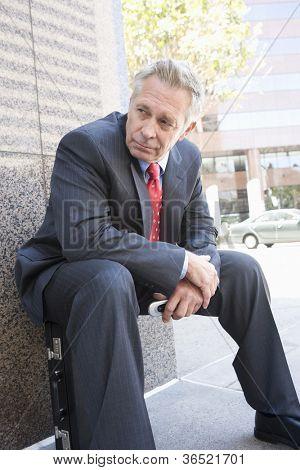 Senior businessman sitting on his briefcase