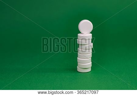 Tower Of White Tablets On A Green Background