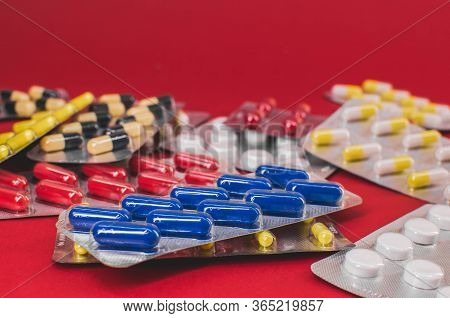 Pile Of Multicolored Tablets On A Red Background