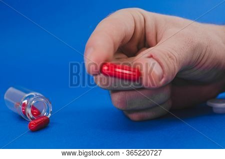 A Mans Hand Is Holding A Red Pill