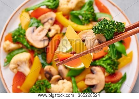 Pad Pak Ruam Or Veg Thai Stir-fried Vegetables Close Up Slices In Chopsticks . Pad Pak Is Thailand C