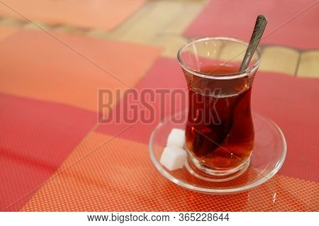 Hot Turkish Tea In Tulip-shaped Glass With Sugar Cubes Isolated On Colorful Luncheon Mats