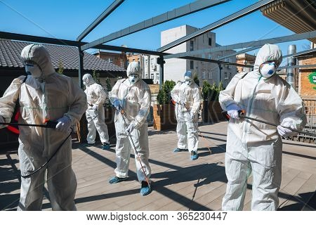 Coronavirus Pandemic. A Disinfectors In A Protective Suit And Mask Spray Disinfectants In House Or O