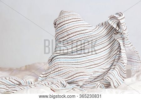 Small Caucasian Boy Playing Under A Striped Blanket On White Bedding