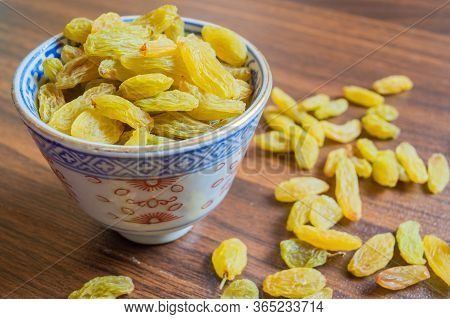 Green Raisins In A  Bowl With Some Raisins On Brown Wooden Background. Copy Space For Text Provided.