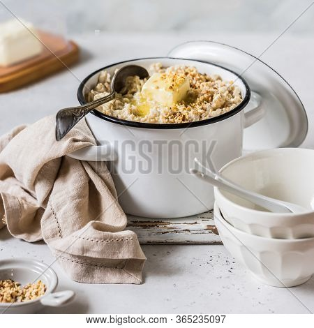Old Fashioned Rolled Oat Porridge With Melting Butter In A Sauce Pan Topped With Chopped Almond Nuts
