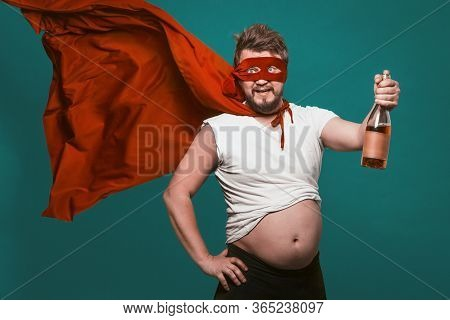 Drunk Superhero Or Antihero Man With Bottle Of Alcohol, Man In Superhero Red Mask And Fluttering Clo