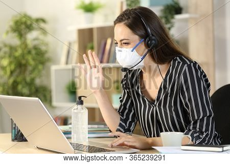 Telemarketer Woman Greeting On Videocall With Laptop Sitting On A Desk At Homeoffice On Coronavirus