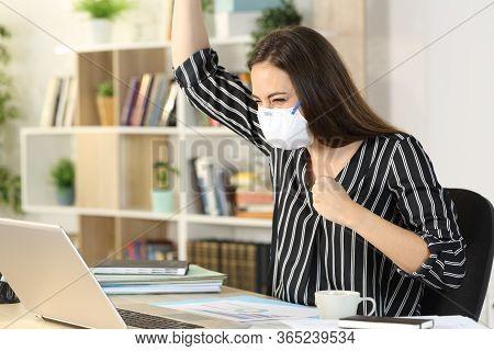 Happy Freelance Woman Celebrating News On Laptop Avoiding Coronavirus With Mask Sitting On A Desk At