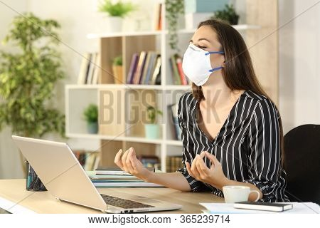 Freelance Woman Stress Relieving Doing Yoga Avoiding Covid-19 With Mask Sitting On A Desk At Homeoff